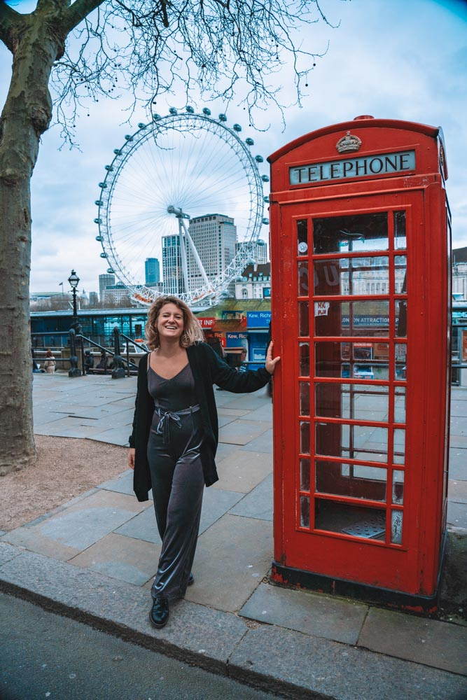 Blonde girl in a grey jumpsuit standing next to a red phone box with London Eye behind her