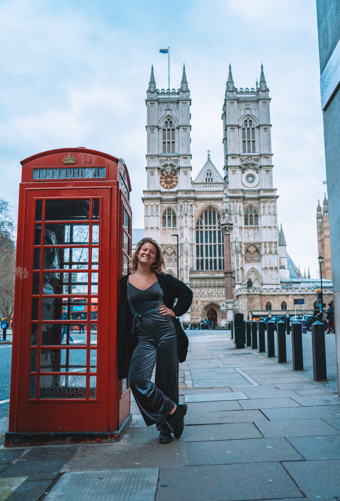 Blonde girl in a grey jumpsuit posing next to a red phone box and Westminster Abbey behind her
