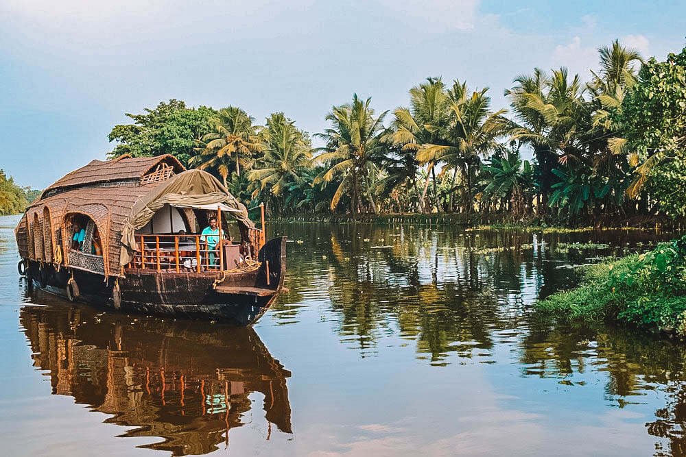 A traditional kettuvallom boat surrounded by the palm trees of the Kerala backwaters