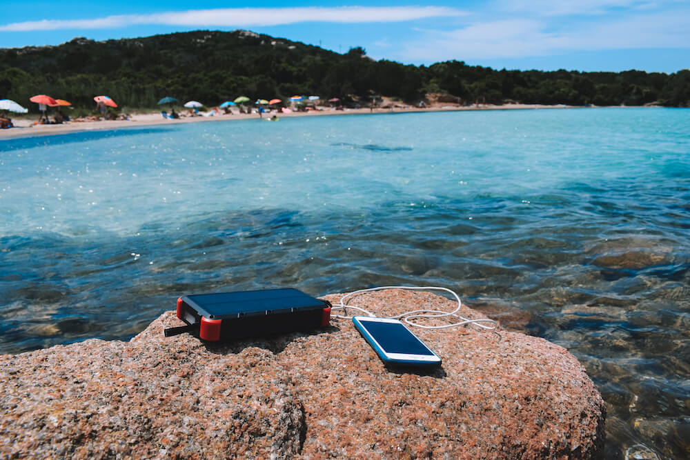 The OUTXE Solar Charger charging my phone at the beach