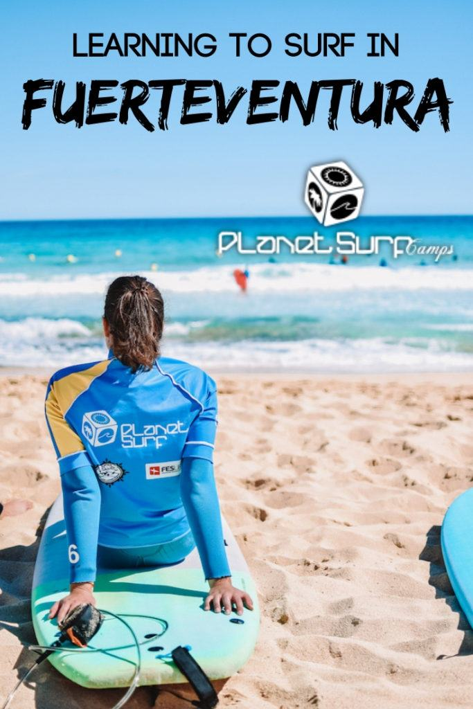 """Brunette girl sat on a surf board watching surfers with text overlay saying """"learning to surf in Fuerteventura"""""""