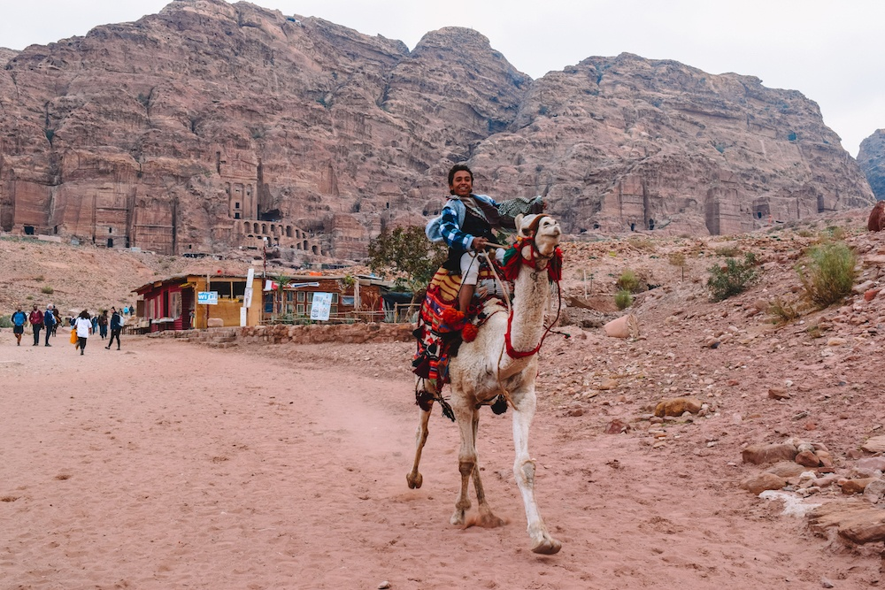 A local kid riding a camel in Petra, Jordan