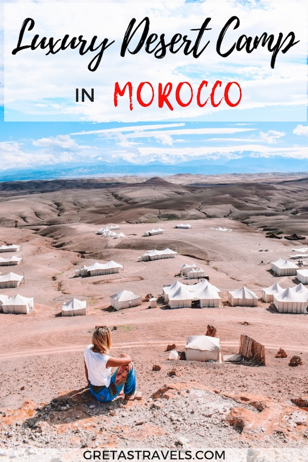 """Photo of a blonde girl sat on op of a hill watching the white tents of Scarabeo Camp below with text overlay saying """"Luxury Desert Camp in Morocco"""""""