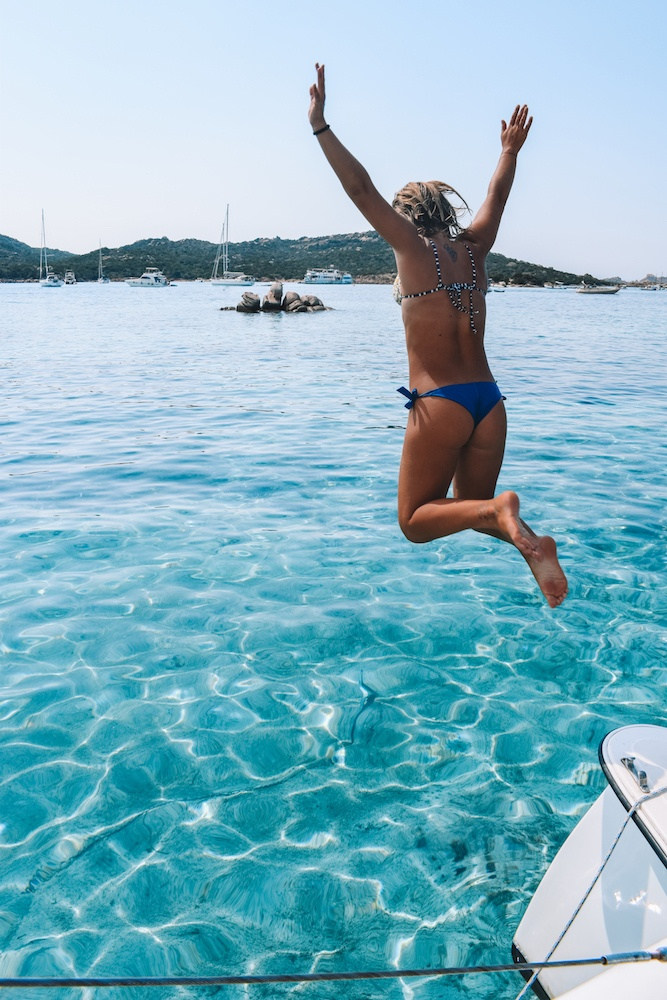 Girl jumping in the clear water of the Maddalena Archipelago