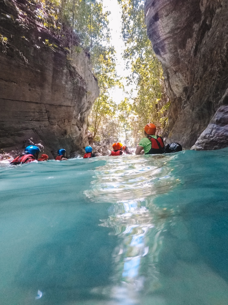 Swimming through a part of the river while canyoning in Kawasan Falls