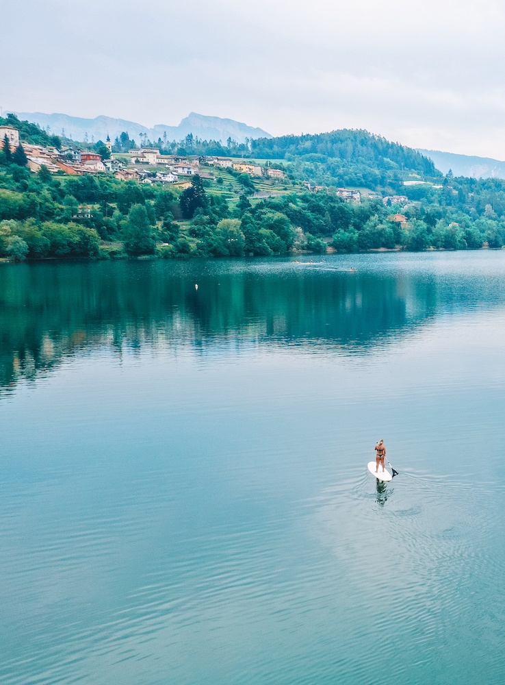 Drone shot of a girl doing SUP in the middle of Lake Caldonazzo in Trentino, Italy, with the mountains in the background and shoreline reflected in the lake