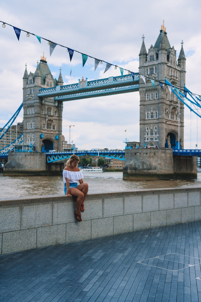 Girl sitting along the River Thames with Tower Bridge behind her