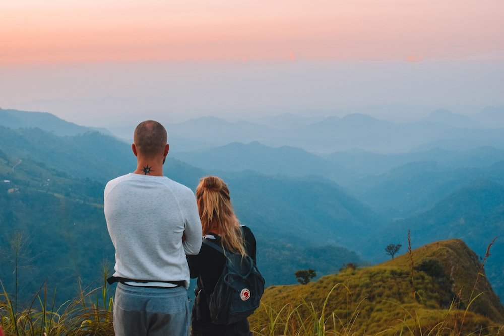 A back shot of a couple at the top of Little Adam's Peak as they watch the sunrise over the hills that surround Ella