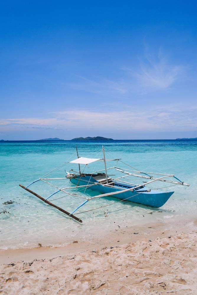 A traditional Filipino boat on the beach in Malcapuya Island