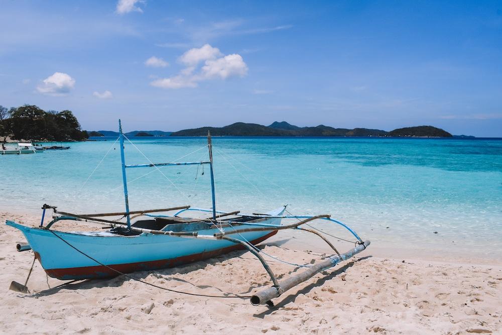 A traditional Filipino boat on the beach on Malcapuya Island