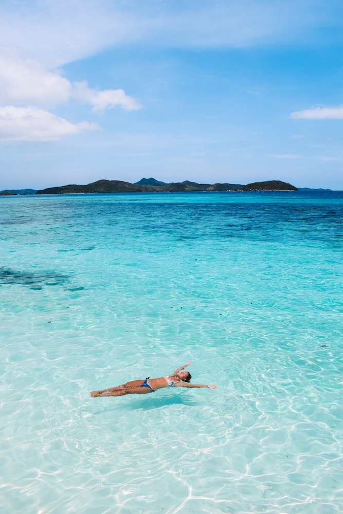 Floating in the clear turquoise water of Malcapuya Island