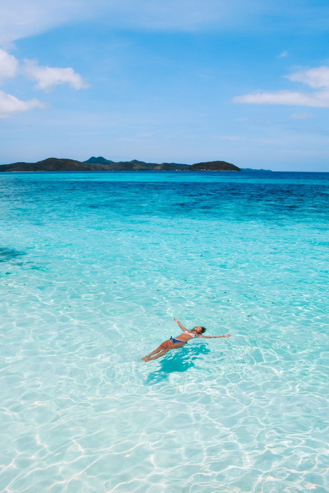 Floating in the crystal clear water of Malcapuya Island