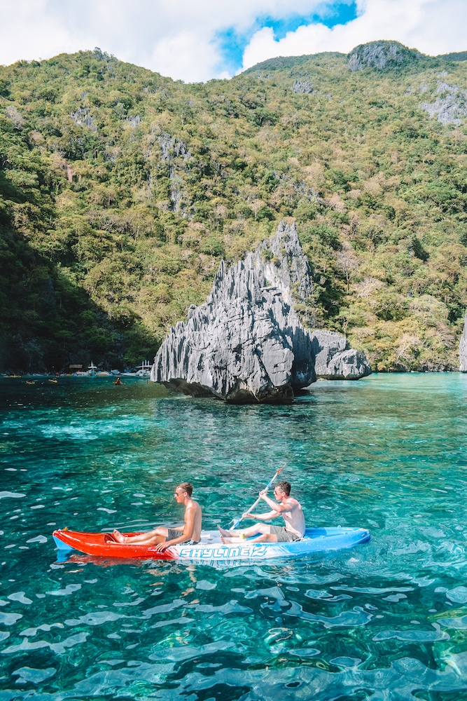 Two boys kayaking in a lagoon in El Nido, with clear turquoise water and limestone cliffs behind them
