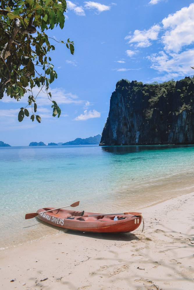 Our kayak on an empty beach in El Nido, with clear turquoise water and cliffs behind it
