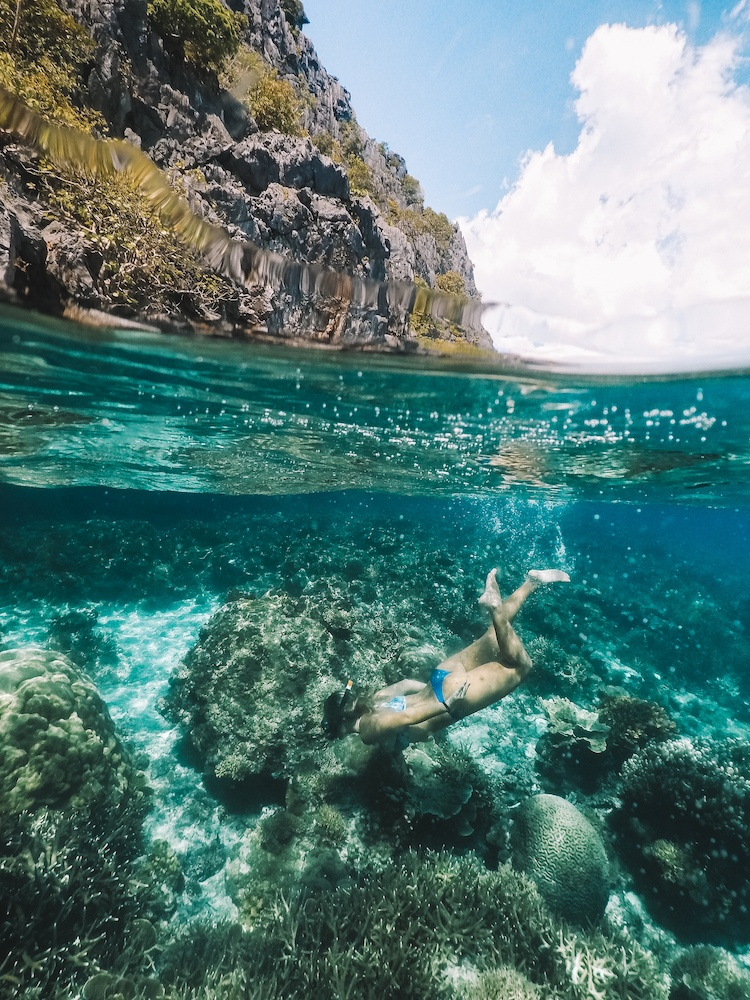 Girl snorkelling in El Nido, Philippines - taken with a GoPro dome, 50/50 with corals under water and steep limestone cliffs over
