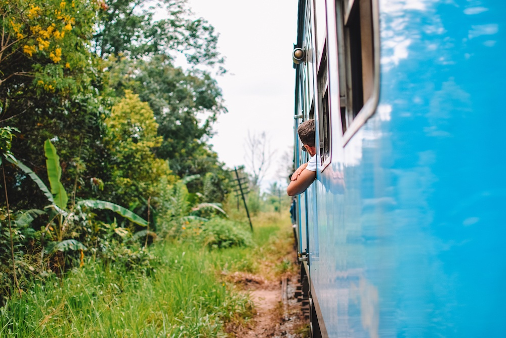 Passengers leaning out from the windows of the turquoise train during the Kandy to Ella train