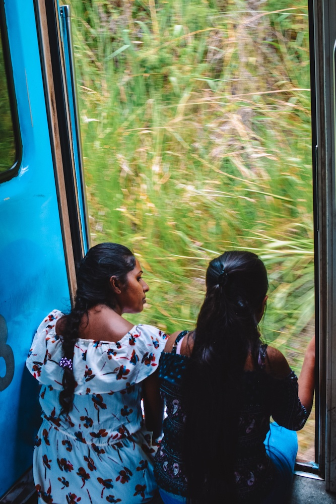 Girls leaning out of the train carriage on the journey from Kandy to Ella