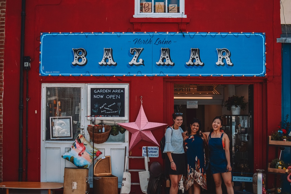 Three girls smiling in front of the red facade of the North Laine Bazaar in Brighton, a famous vintage shop