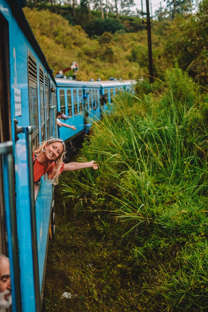 Blonde girl leaning out of the window of the turquoise train and smiling at the camera. There are green tea plants visible, typical of the views during the Kandy to Ella train journey