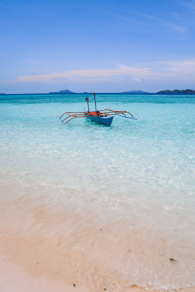 A traditional Filipino boat close to the shore of Malcapuya Island