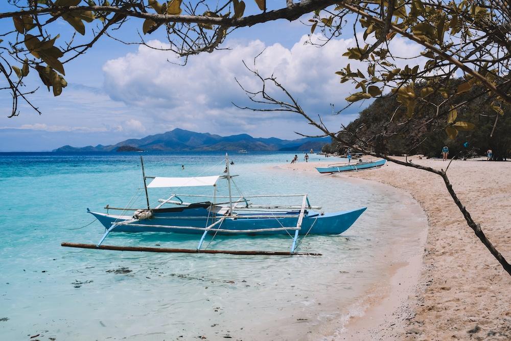 Traditional Filipino boats on the beach at Malcapuya Island