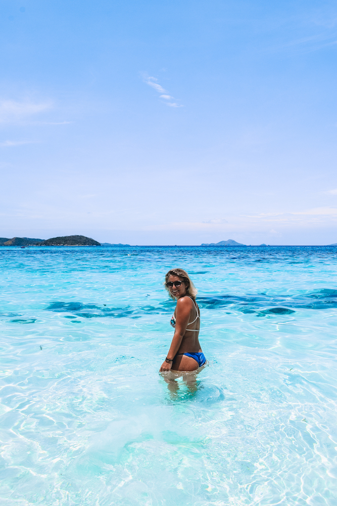 Girl walking in the clear turquoise water of Malcapuya Island, Philippines