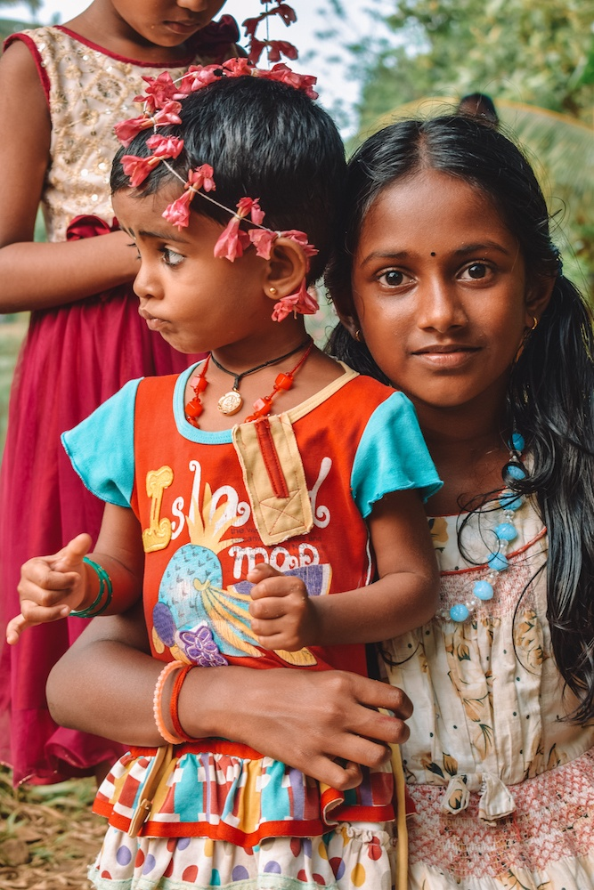 Two young girls in colourful outfits in a village in Kerala, India