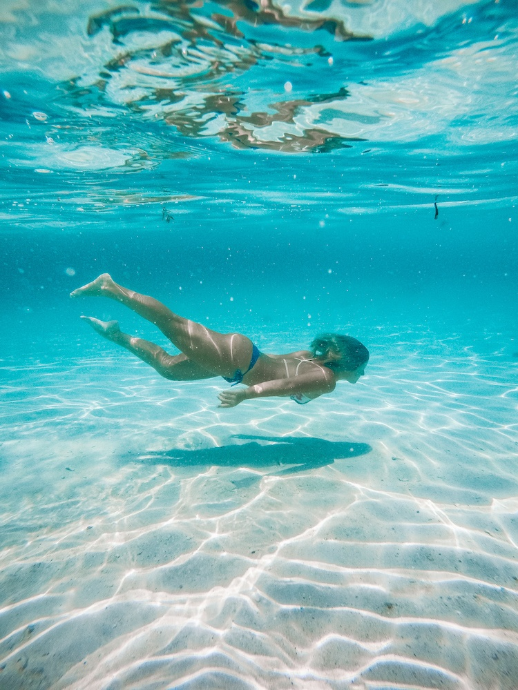 Underwater GoPro shot of a girl swimming in the crystal clear water of Malcapuya Island
