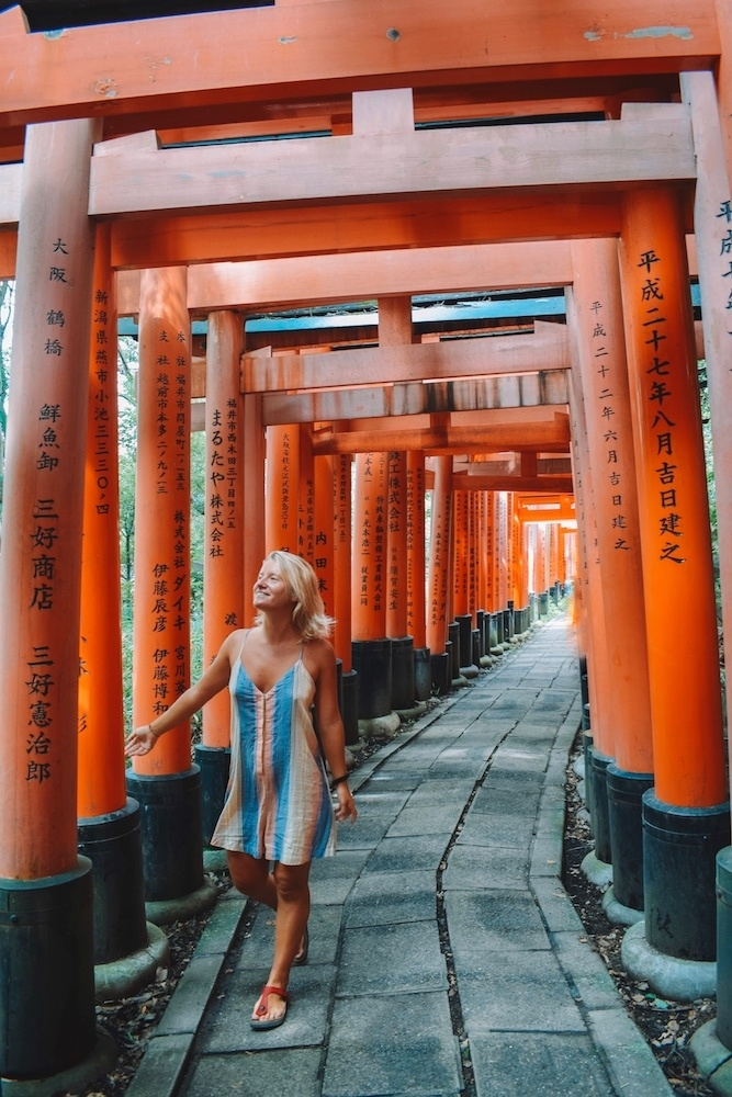 Blonde girl in a colourful jumpsuit walking through the red torii gates of Fushimi Inari-Taisha in Kyoto, Japan