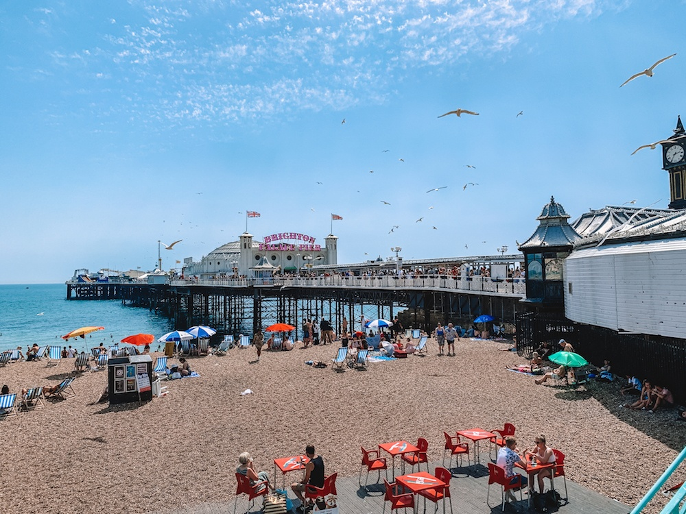 The beach in Brighton just under Brighton Palace Pier, busy with people, umbrellas and seagulls flying around on a sunny day