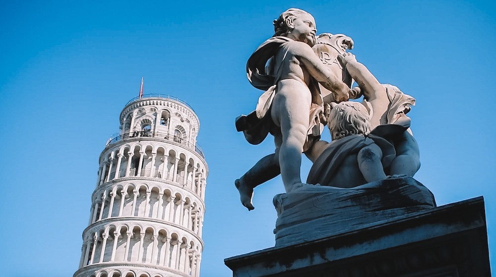 The Leaning tower of Pisa with the statue of three angels close to it