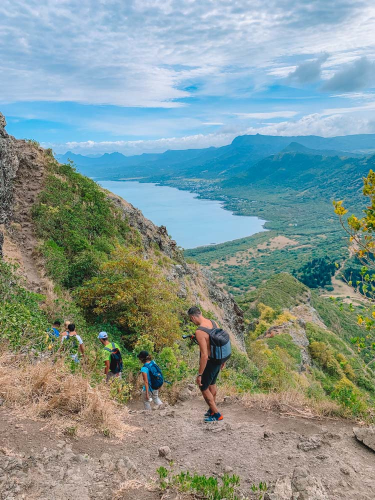 A group of people hiking in single line up Le Morne Brabant, Mauritius