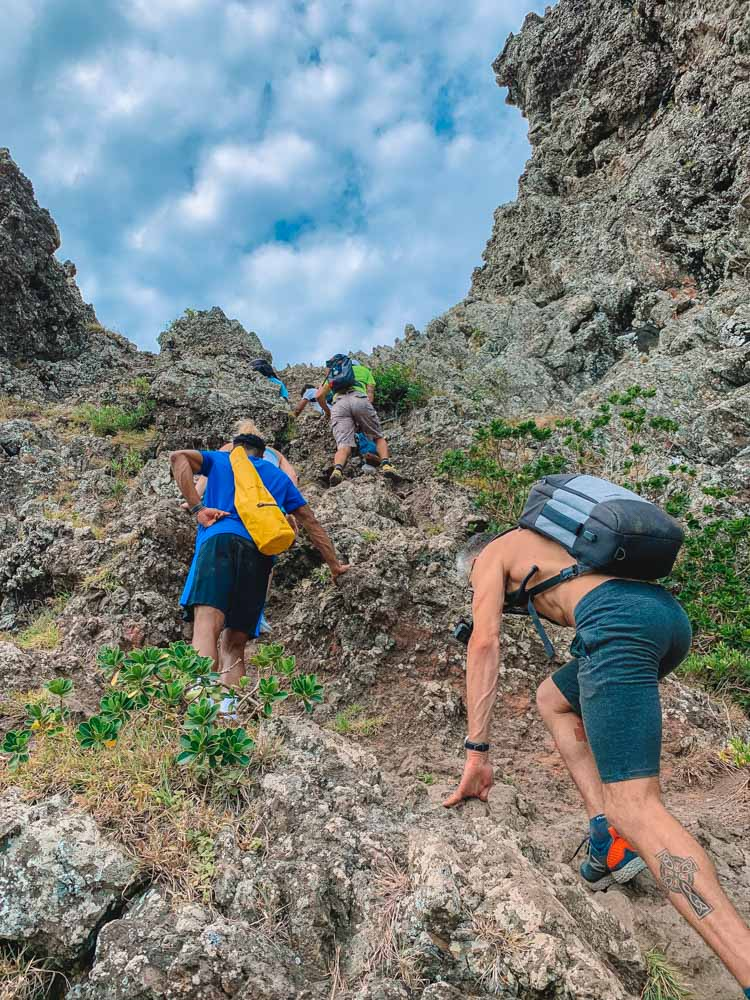 Three people climbing their way up Le Morne Brabant in Mauritius - this is the tough part where you need to help yourself with your hands