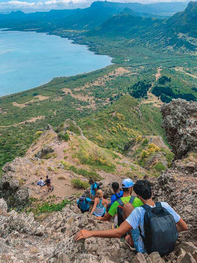 Single file group of people as they slowly climb back down Le Morne Brabant in Mauritius