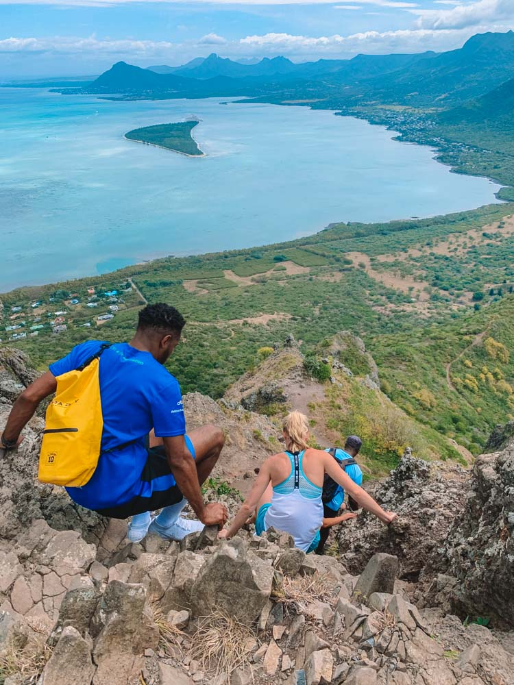 People sat on the rocks as they climb their way back down Le Morne Brabant, there are views over the bay of Mauritius behind them