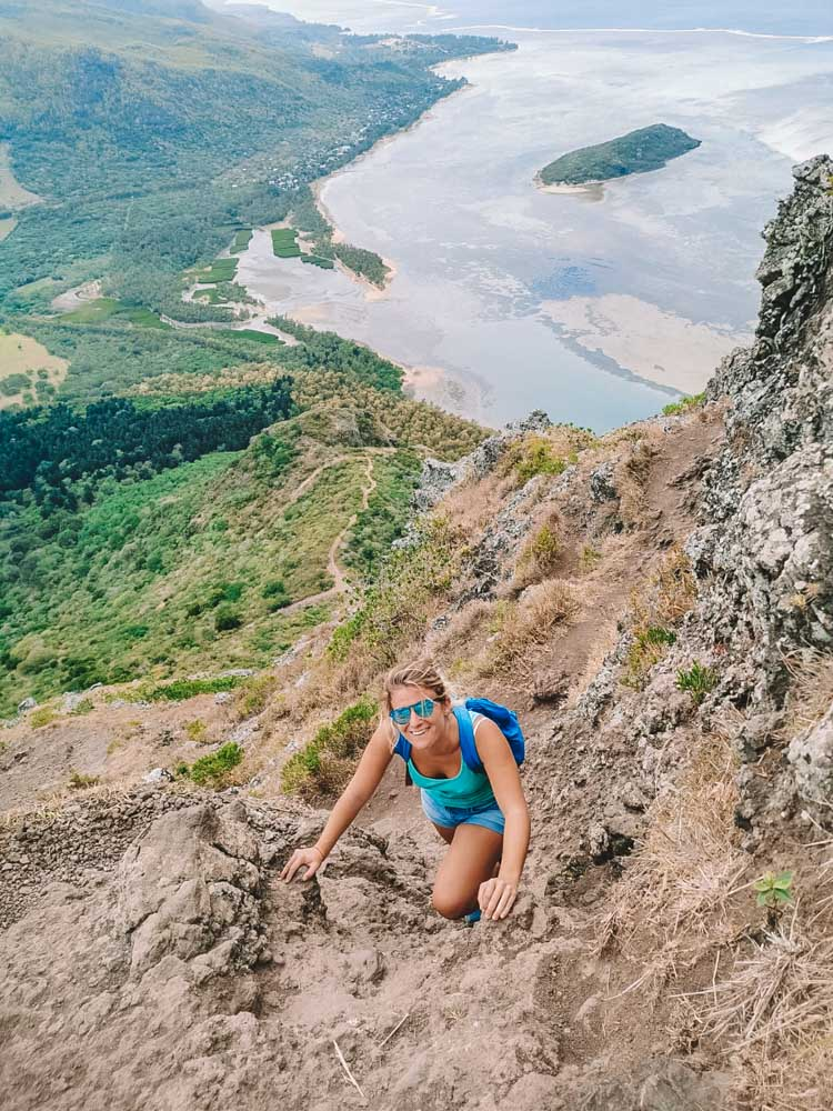 Blonde girl climbing up Le Morne Brabant helping herself with her hands