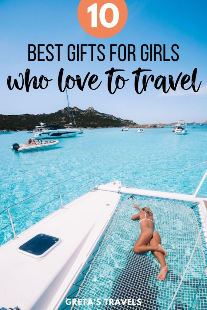 """Girl laying on the nets of a catamaran in the sea with super clear blue water and text overlay saying """"10 best gifts for girls who love to travel"""""""