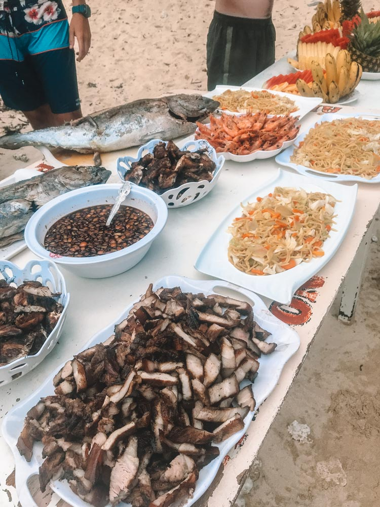 A big table and buffet with grilled fish, pork, noodles and rice served on the beach in El Nido