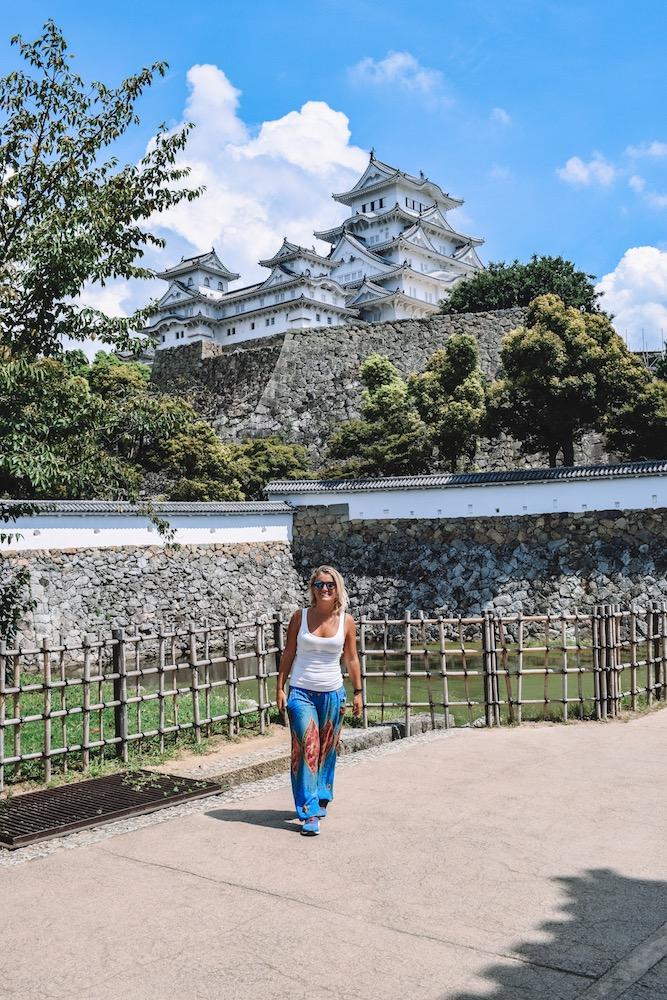 Blonde girl standing in front of Himeji Castle in Japan