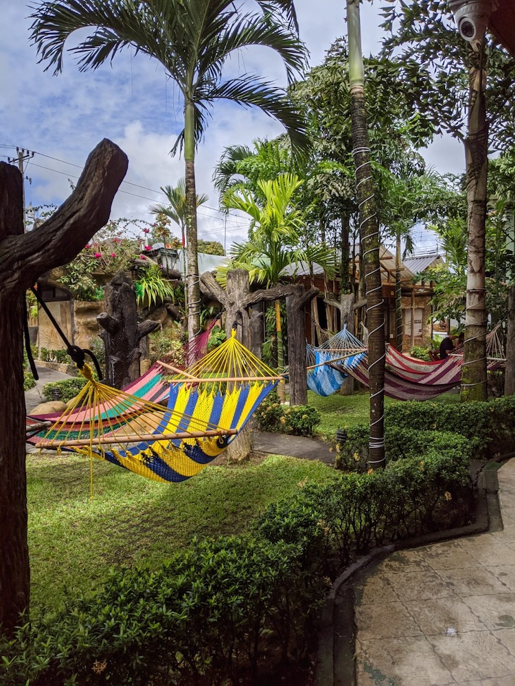 The courtyard area with hammocks of Arenal Hostel Resort
