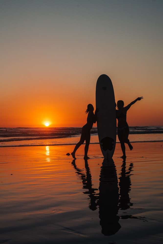 Surfing in Santa Teresa Beach at sunset, Costa Rica