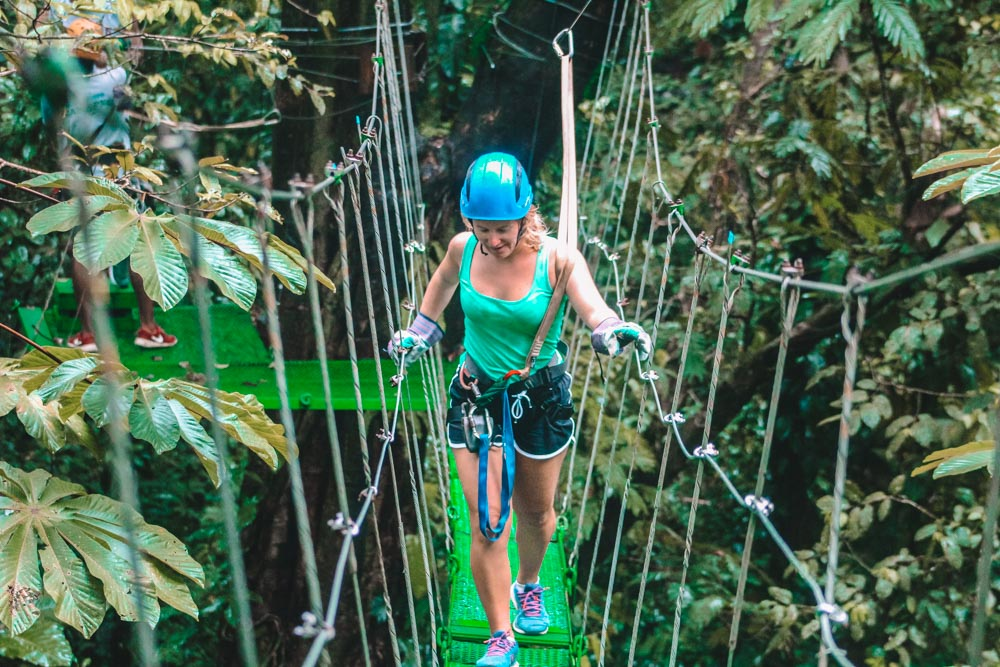 Blonde girl walking across a hanging bridge at the top of rainforest treetops in Tortuguero National Park