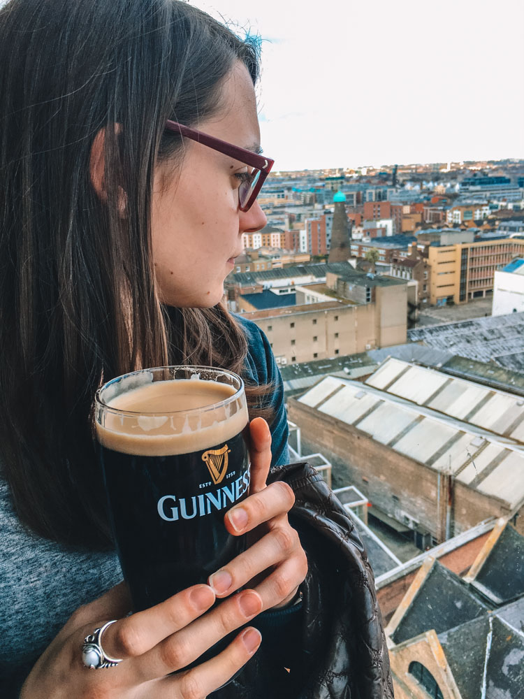 My friend Laura drinking a pint of Guinness while enjoying the view over Dublin