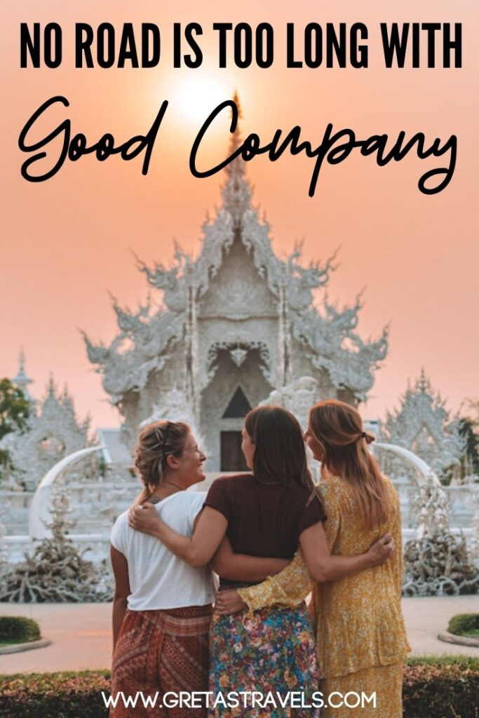 """Photo of three girls standing hugging each other in front of the White Temple in Chiang Rai, Thailand, with text overlay saying """"No road is too long with good company"""" - one of my favourite quotes about travelling with friends!"""