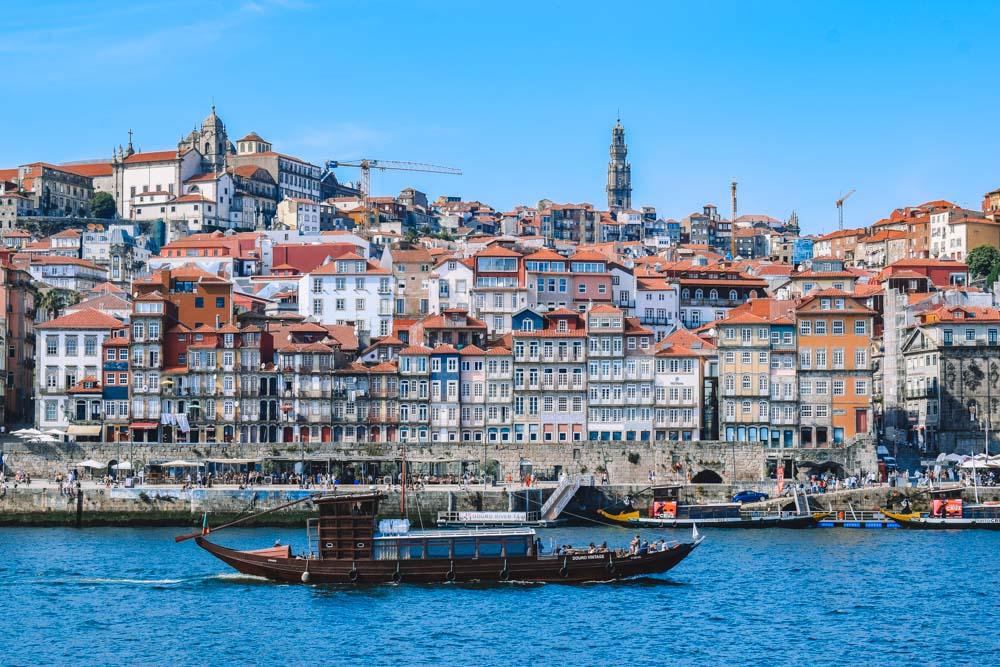 A traditional rabelo boat cruising along the Douro River with the recognisable Porto skyline behind it
