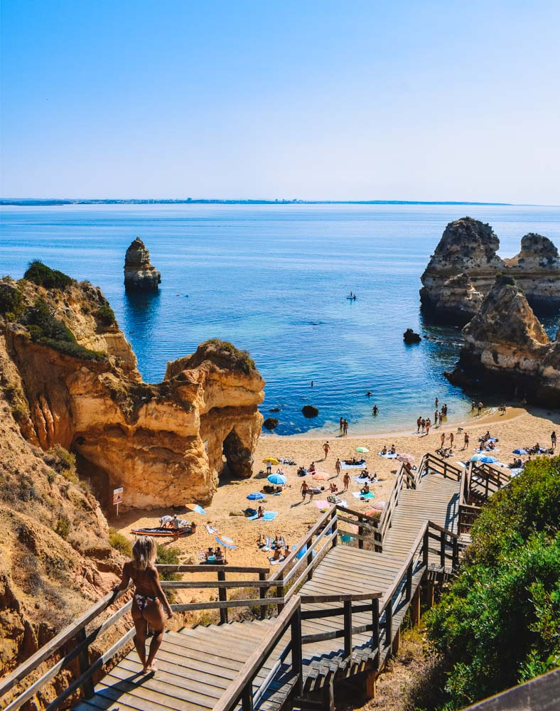 Walking down the famous wooden stairwell of Praia do Camilo in Portugal